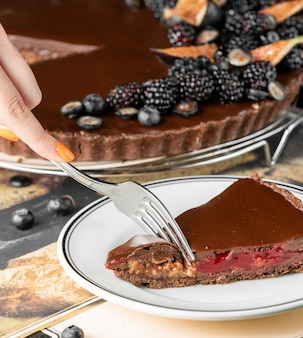 Woman cutting a piece of chocolate cheesecake with raspberry and nuts