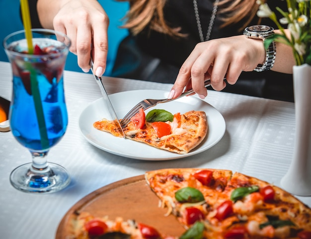 Woman cutting pizza slice with cutlery and a glass of blue lagoon cocktail standing around.