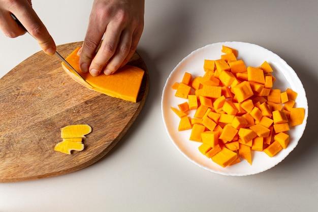 カボチャを切る女性。家庭料理。持続可能な消費食品