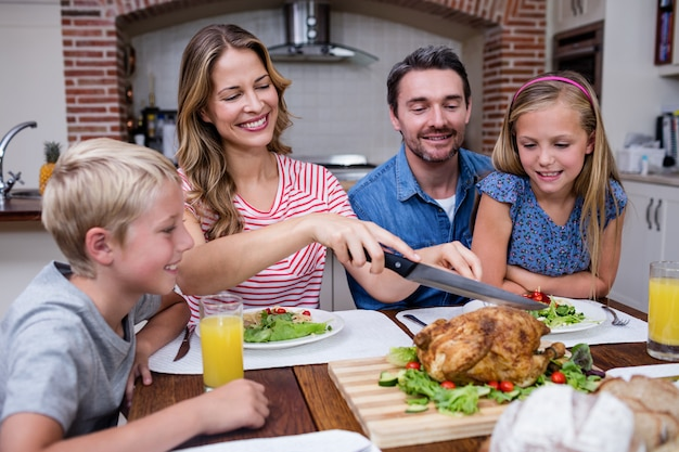 Woman cutting roasted turkey while having meal with his family