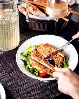 Woman cutting sesame crusted chicken served with salad