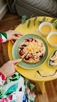 Woman cutting a slice of plum crumble pie