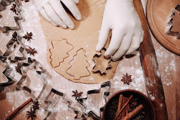 金属製のクッキーカッターでジンジャーブレッド生地を切る女性