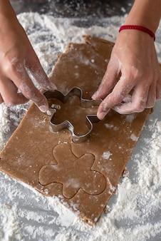 金属のクッキーカッターの男といくつかのジンジャーブレッド生地を切る女性