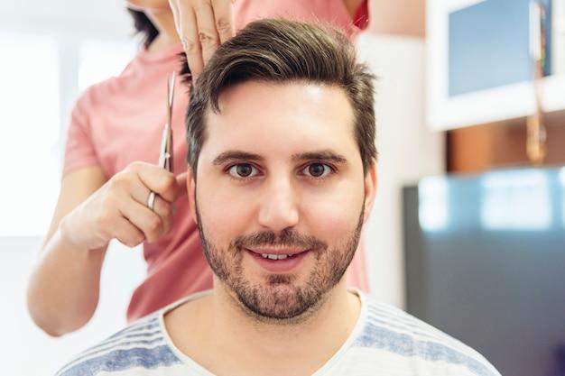 Женщина подстригает волосы молодого человека в кустарной парикмахерской дома