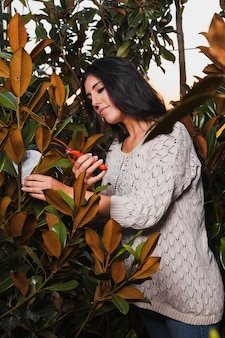 Woman cutting twigs with pruner