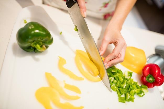 Женщина резки овощей на разделочной доске