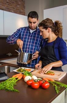 夫が食べ物と一緒に鍋を見せている間に野菜を切る女性