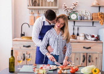 Woman cutting vegetables while man hugging her