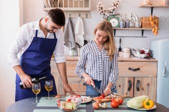 Woman cutting vegetables while man pouring wine in glass