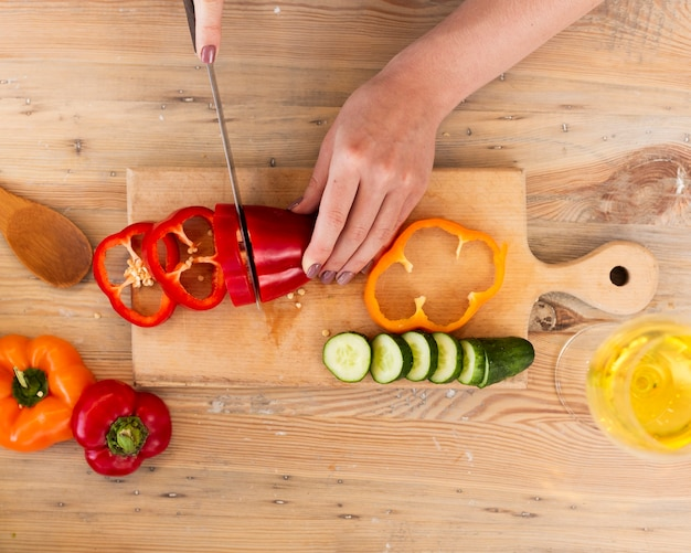 Woman cutting vegetables on a wooden tray