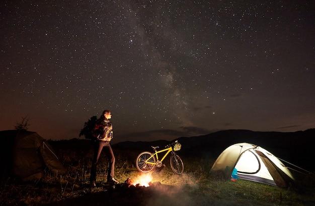 Велосипедист женщина в ночном кемпинге возле горящего костра