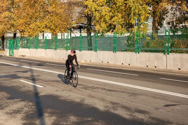 女性サイクリストは晴れた秋の朝にトレーニングを行います