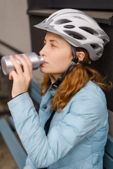 Woman cyclist in a helmet drinking water