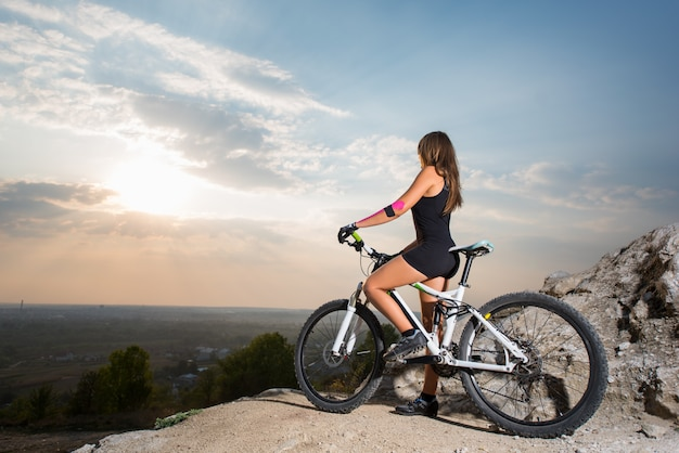 Woman cyclist on a mountain bike on the cliff at the sunset