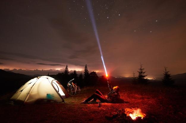 Woman cyclist at night camping near burning campfire