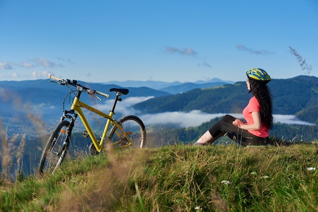 Woman cyclist riding on bicycle in the mountains