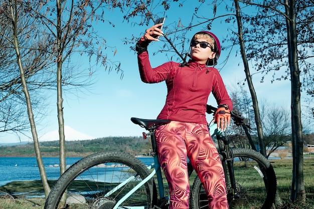 夏の間に自然公園で休んで自分撮りをしているヘルメットを持つ女性サイクリスト