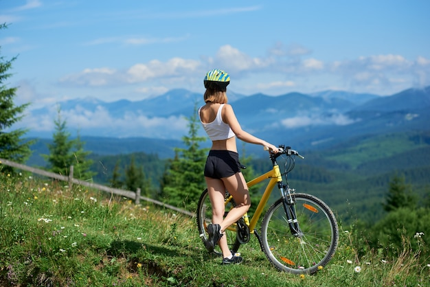 Woman cyclist with yellow bicycle