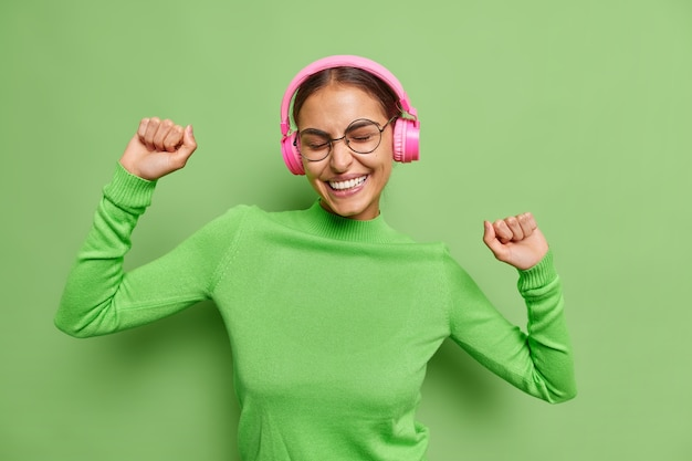 Woman dances carefree raises arms feels glad catches every bit of music listens music in wireless headphones wears turtleneck spectacles on green