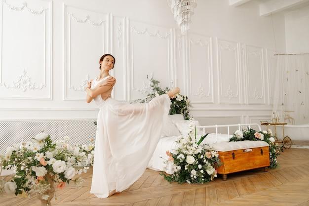 Женщина танцует в белом платье с цветами
