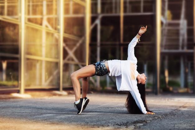 Женщина танцует на уличной платформе в летний солнечный вечер