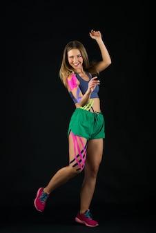 어둠 속에서 춤추는 여성, 키네시오 테이프가 그녀의 몸에 붙어 있습니다. 스포츠와 건강한 라이프 스타일 컨셉