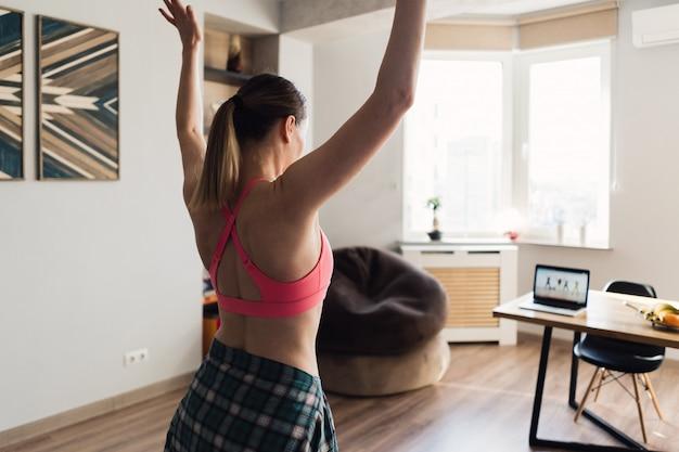 Donna che balla a casa seguendo le video lezioni sul computer portatile