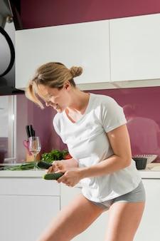 Женщина танцует на кухне и держит огурцы