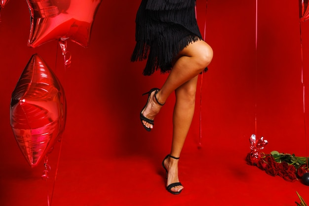 赤い背景で踊る女性黒いバソの脚で美しい女性の脚お祭り気分風船...