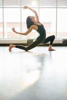 Woman dancing in sunlit studio