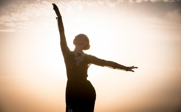 Woman dancing at sunrise