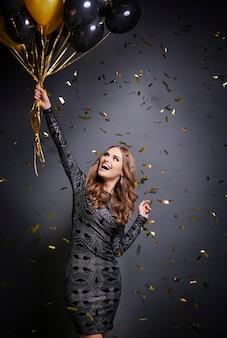 Женщина танцует с воздушными шарами в серой стене