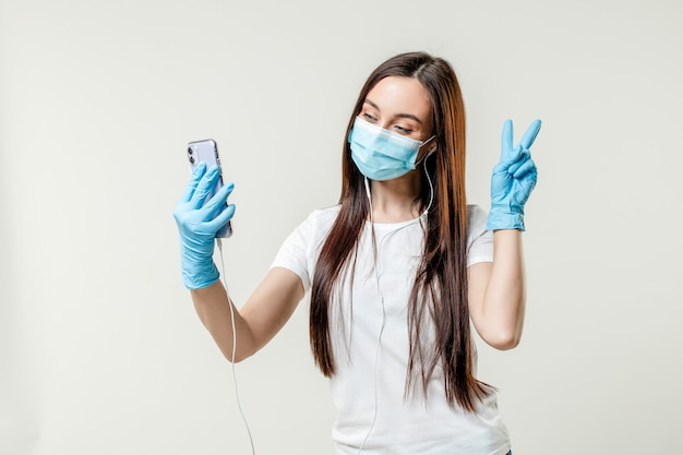 Woman dancing with earpods wearing mask and gloves