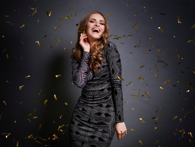 Женщина танцует с падающим конфетти