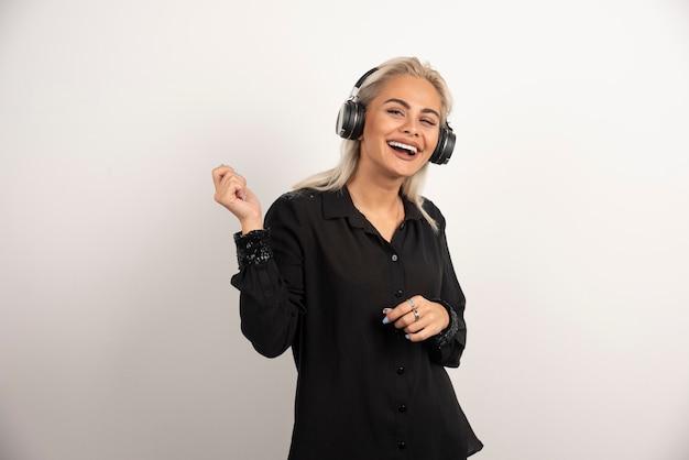 Donna che balla con il ritmo della musica su sfondo bianco. foto di alta qualità