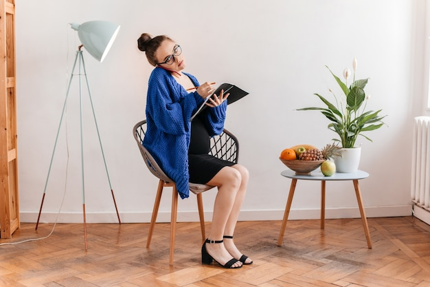 Woman in dark blue knitted cardigan talks on phone and makes notes. pregnant lady sits on wooden chair and holds notebook.