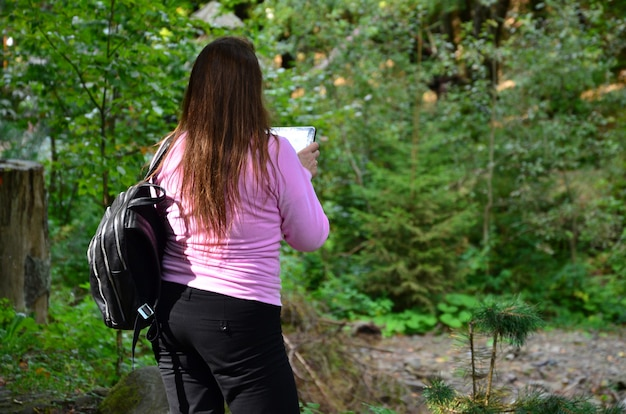 A woman in dark trousers and a pink sweatshirt admires the mountain river