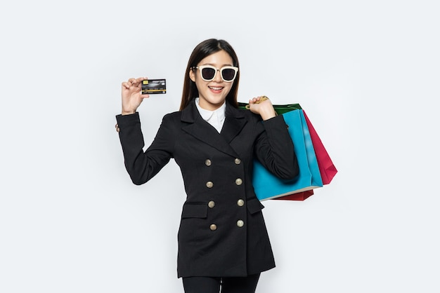 Woman in dark wear glasses, go shopping, carries credit cards, and lots of bags