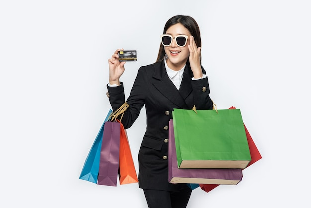 Woman in dark wear glasses, go shopping, carry credit cards, and lots of bags