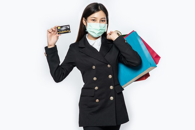 A woman in dark and wearing a mask walks shopping, carries credit cards, and lots of bags