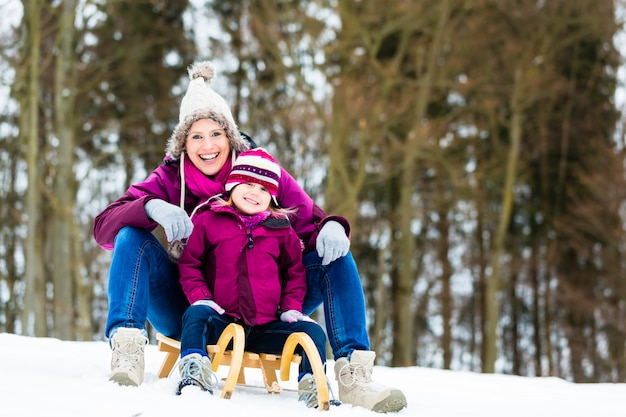 Woman and daughter on sled in winter