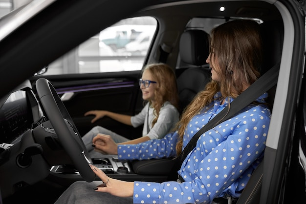 Woman and daughter testing new expensive automobile.