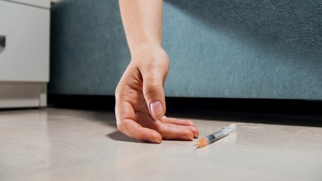 Woman of dead woman with drugs addiction lying on floor with syringe.