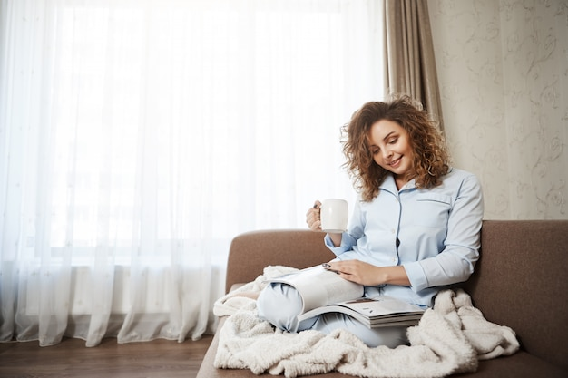 Woman decided to treat herself in bright good day. portrait of attractive female curly-haired female sitting on sofa in pyjamas, drinking coffee, enjoying reading magazine, covering feet with blanket