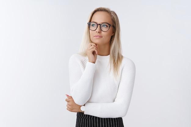女性は、あごに触れ、考え、数えながら、思慮深い視線で目をそらし、白い背景の上に眼鏡やオフィスの衣装でポーズをとることで、売上と収入をどのように改善するかを決定します。コピースペース