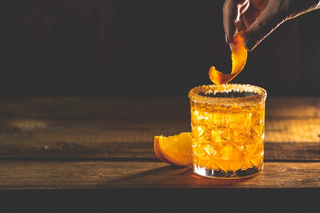 女性は、古い木の板にオレンジツイストアルコールカクテルネグロニを飾ります。 1919年にイタリアのフィレンツェで最初に混合されたジン、カンパリマティーニロッソ、オレンジ、イタリアンカクテル、食前酒と一緒に飲む