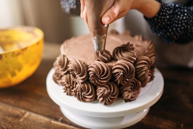 Женщина украшает торт кулинарным шприцем