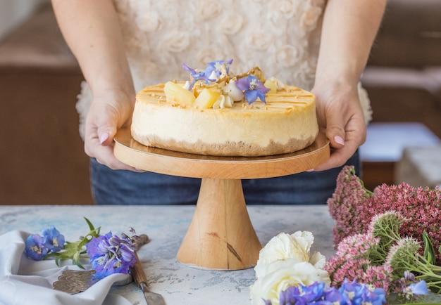 女性は、キャラメルアップルチーズケーキを装飾されています。