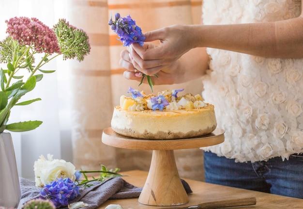 Woman decorated caramel apple cheesecake.